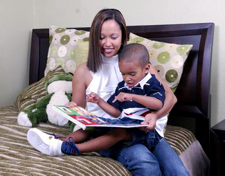 A woman with a boy is reading a book.