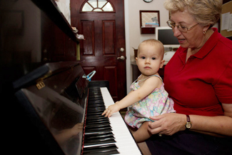 Lady with baby sits in front of piano