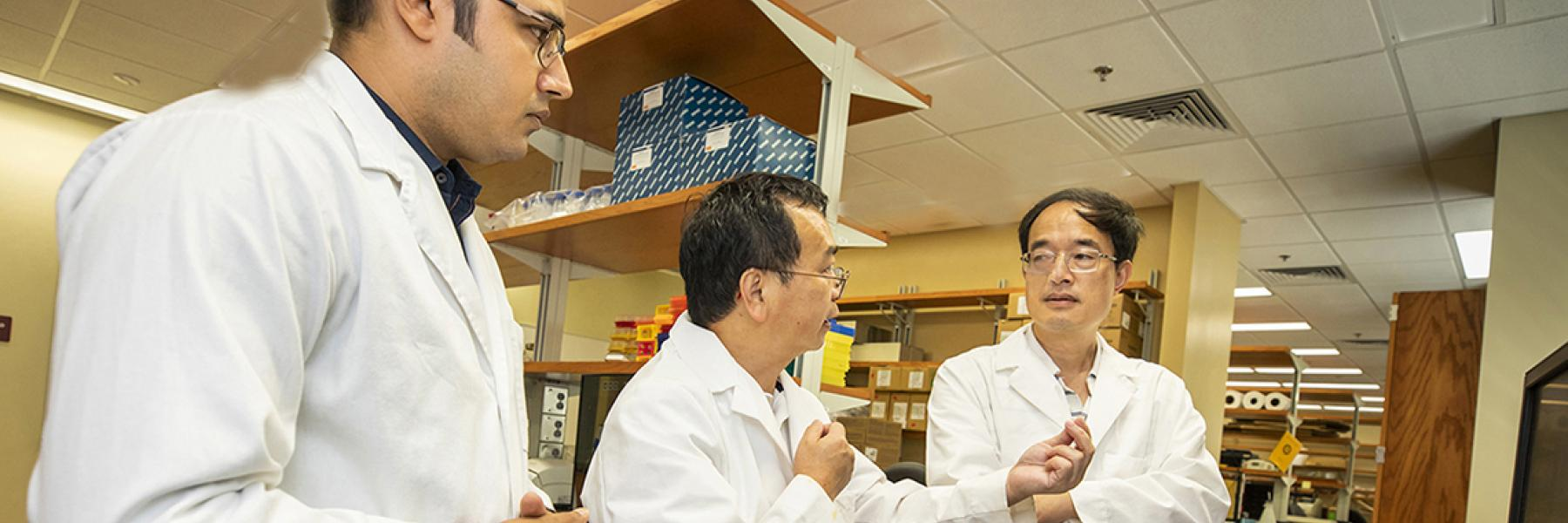 Zucai Suo, right, in his lab at the College of Medicine.