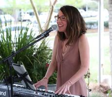 Cathy Levenson, PhD playing the keyboards and singing at our 2019 Wine Tasting Gala.