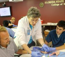 Dr. Julia Weeks instructs 3rd year students Brian Day and Jimmy Brown on Dermatology procedures.