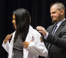 Michael Nair-Collins, Ph.D. coated his wife, Sangeeta Nair-Collins (M.D., '18), at the White Coat Ceremony in 2015